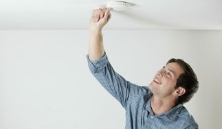 Man checking smoke alarm